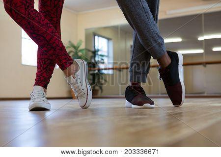 Low section of friends practicing dance on wooden floor in studio