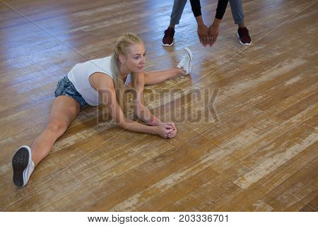 Full length of female dancer with friend stretching legs on floor in studio