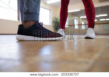 Low section of man with female friend rehearsing dance in studio