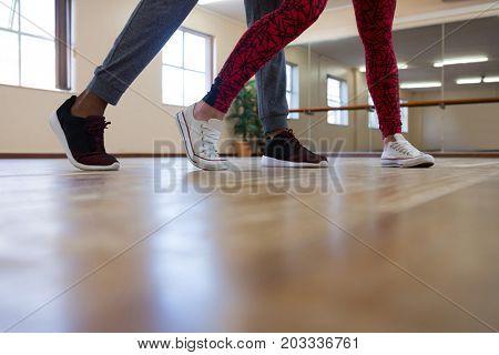 Low section of friends dancing on hardwood floor in studio