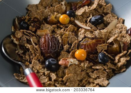 Close-up of wheat flakes with blueberry and golden berry in bowl