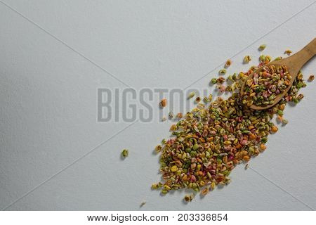 Breakfast cereals scattered from spoon on white background