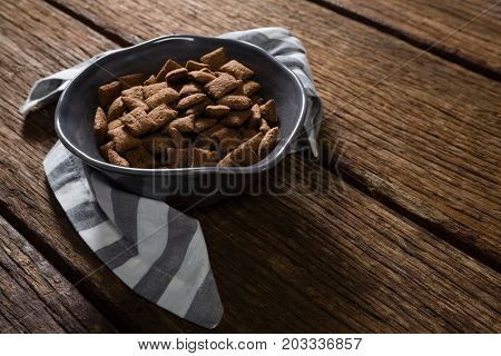 Bowl of chocolate toast crunch with napkin on wooden table