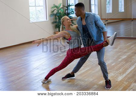 Full length of young friends practicing dance in studio