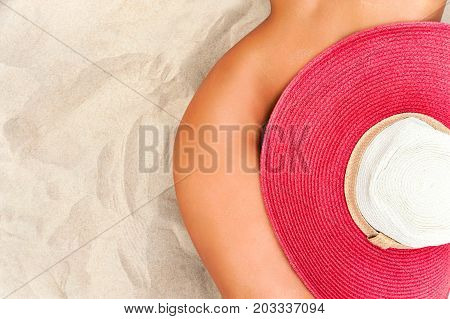 Hot summer tanned body. Naked woman body curves. Hips and waist covered with red straw summer hat.
