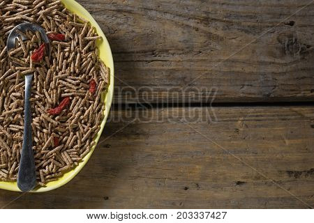 Cereal bran sticks with spoon in plate on wooden table