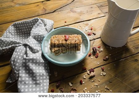 Close-up of granola bar and milk in bowl