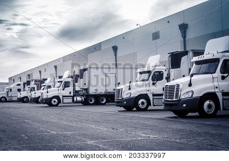 Delivering or Supply concept image.  Trucks loading at facility.