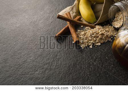 Close-up of banana, oatmeal, cinnamon sticks on black background