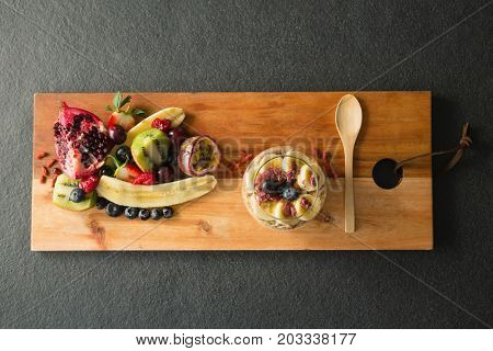 Various fruits on chopping board on black background