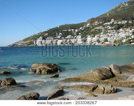 CLIFTON, CAPE TOWN, SOUTH AFRICA,  WITH BOULDERS IN THE FOREGROUND AND A MOUNTAIN IN THE BACKGROUND
