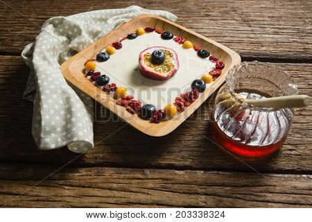 Close-up of fruit yogurt and honey on a wooden table