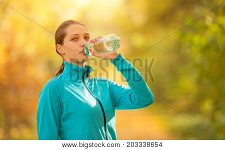 Young woman drinking fresh water from bottle during her fitness exercise in autumn. Lifestyle and sport photo of healthy style. Outdoor and nature fitness.