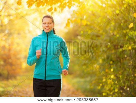 Young brunette woman running in autumn forest. Lifestyle and sport photo of healthy style. Outdoor and nature fitness exercise.