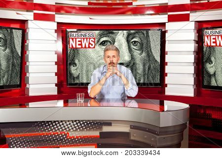 Business news. A television anchorman at studio during live broadcasting