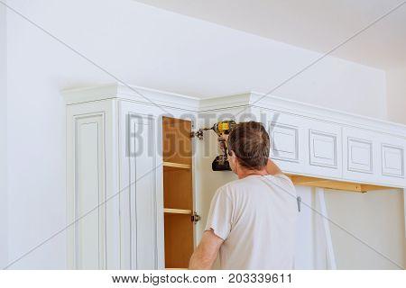 Technician Man Installing Kitchen Cabinets