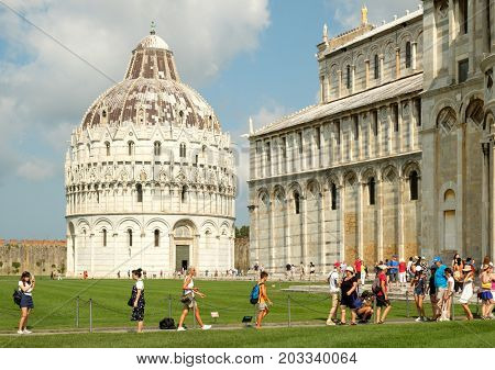 PISA,ITALY - JULY 23,2017 : Tourists next to the Cathedral at Piazza del Duomo in Pisa