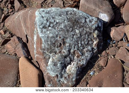 Traces of amethysts on fragment of rock of red sandstone on the shore of the Tersky coast at low tide on the site of former developments of the amethyst brush