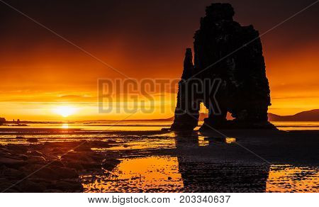 Is a spectacular rock in the sea on the Northern coast of Iceland. Legends say it is a petrified troll. On this photo Hvitserkur reflects in the sea water after the midnight sunset