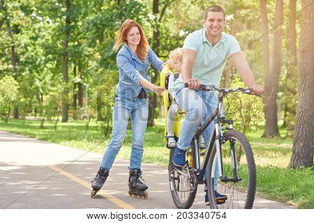 Shot of a happy man riding bicycle at the park with his baby in a bike seat and his wife rollerblading copyspace family activity sports recreation leisure weekend holidays.