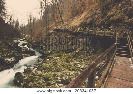 Scenery of curved wooden bridge with clear stream flow rock and brown forest background in winter, View of wood walkway path with water stone canal and leaves of tree in Bled at Slovenia