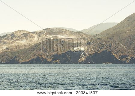 sea, mountains and marble quarry landscape, view from sailboat