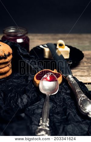 Spoon With Jam Near Chocolate Cookies And Biscuits On Black Table Background. Afternoon Break Time.