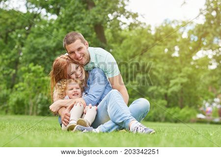 Shot of a happy young loving family having fun outdoors sitting on the grass at the park on a warm summer day hugging and cuddling copyspace parents love couples children kids daughter father mother.