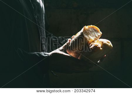 Loaf of fresh baked wheat bread in man's hands in sunshine. Rustic day light in dark room.