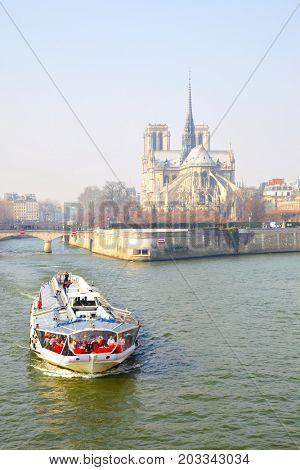Paris, France - March 05, 2011: Tourist recreational boat floats near Notre Dame de Paris