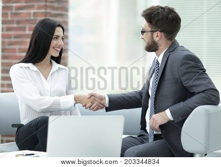 handshake of manager and client sitting in the office lobby.