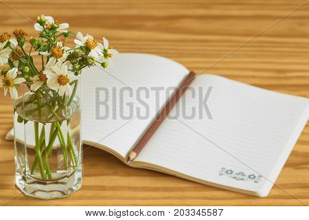 White notebook open on rustic wood table with brown or black pencil. Notebook open on desk with pencil and vase of chamomile so freshness and relax. Copy space concept for background or wallpaper. Copy space background concept for business.