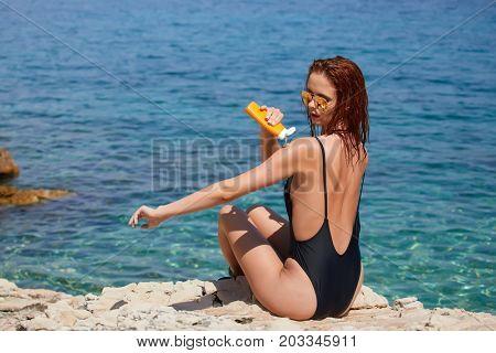 Girl in bikini applying sun lotion at seaside