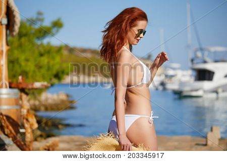 redhair woman in bikini relaxed on quiet sea with warm sunset colors.