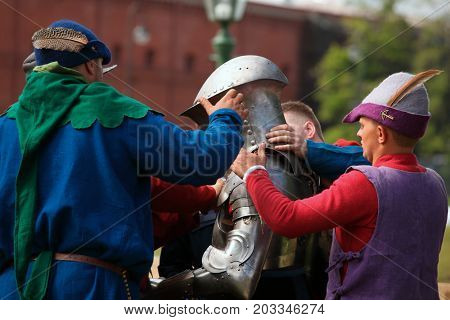 ST. PETERSBURG, RUSSIA - JULY 8, 2017: Armored knight preparing to the battle during the military history project Battle On Neva at St. Peter and Paul fortress. It's the 4th such event