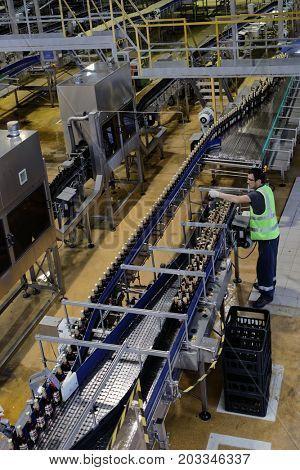 ST. PETERSBURG, RUSSIA - AUGUST 11, 2016: Worker at beer conveyor in the Heineken brewery. It was the first Heineken brewery in Russia, and now it can produce over 5 millions HL of beer per year