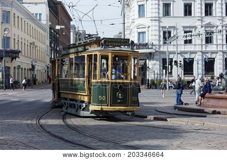 HELSINKI, FINLAND - JULY 29, 2017: Retro tram on Kauppatori, Market Square in a summer day. The car made in 1909 is now used as sightseeing tram route
