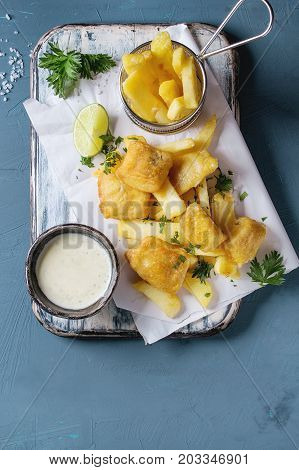 Traditional british fast food fish and chips. Served with white cheese sauce, lime, parsley, french fries in frying basket on white paper over blue concrete background. Top view, copy space