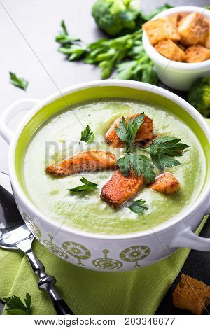 Green soup puree or cream soup with broccoli and salmon on black table. Vertical.