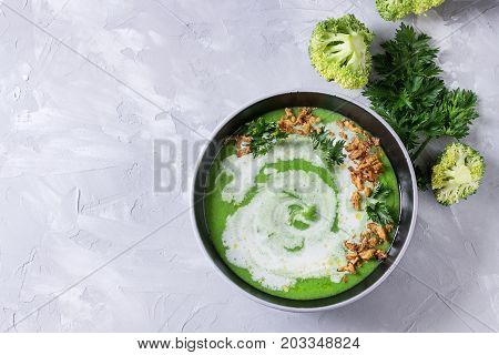 Vegetarian broccoli cream soup served in black bowl with cream, fried onion, fresh parsley and broccoli over over gray concrete background. Top view with space. Healthy eating.