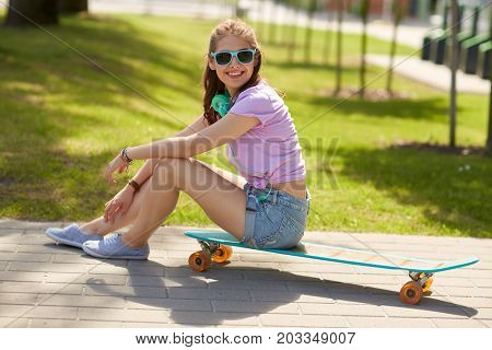lifestyle, leisure and people concept - smiling young woman or teenage girl in sunglasses with headphones sitting on longboard in park