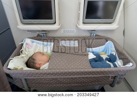 Asian adorable baby boy sleeping In special bassinet on airplane.
