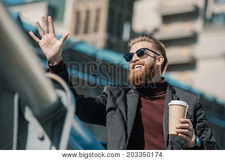 young man with disposable cup of coffee outdoors