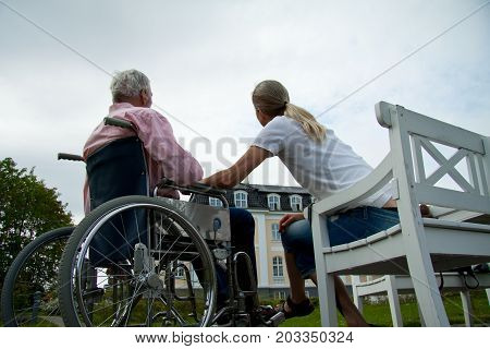 Young woman daughter with senior father in wheelchair at nursing retirement home, Humlebaek, Denmark, May 25, 2010