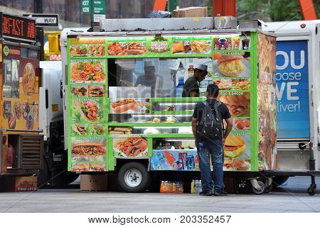 NEW YORK CITY USA - AUG. 23 : Street food cart in Manhattan on August 23 2017 in New York City NY. Manhattan is the most densely populated borough of New York City.