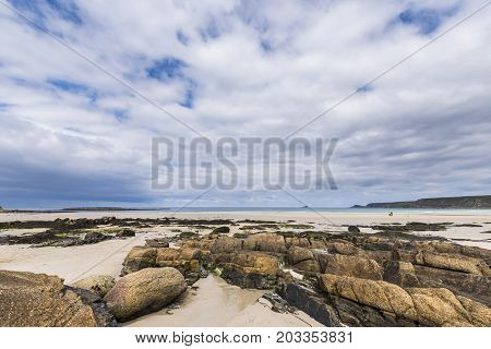 Sennen England - April 27 2017: Rocks at the Sennen Cove beach in Cornwall England wit a small island in the far distance.