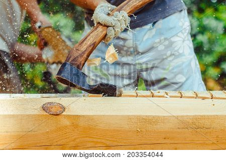 Hands of a strong man splitting wood with an axe focus is on the axe motion freezing in the moment it split