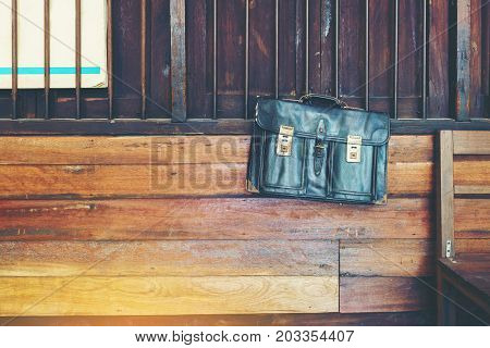 Vintage old black artificial leather Thai schoolbag hanging on iron bar and wood wall