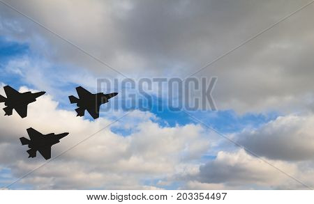Silhouettes of three F-35 aircraft against the blue sky and white clouds
