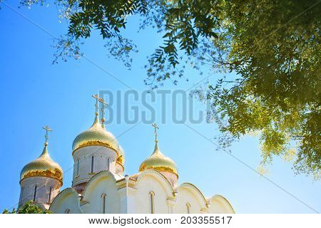Golden domes of the Orthodox church against the blue sky on a sunny day.
